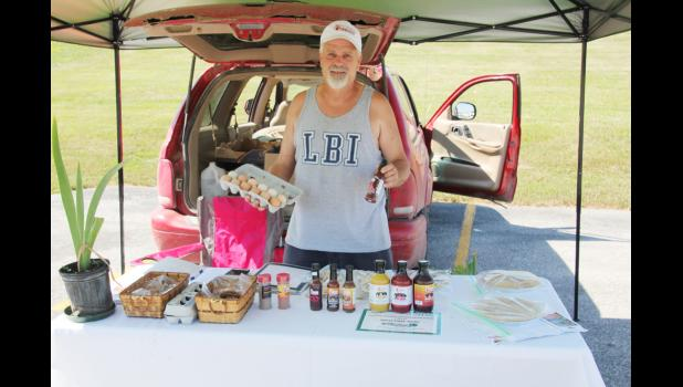 Joe Wilson shows off some of the goods he's selling at the farmer's market.  (Photo by Sarah Muller)