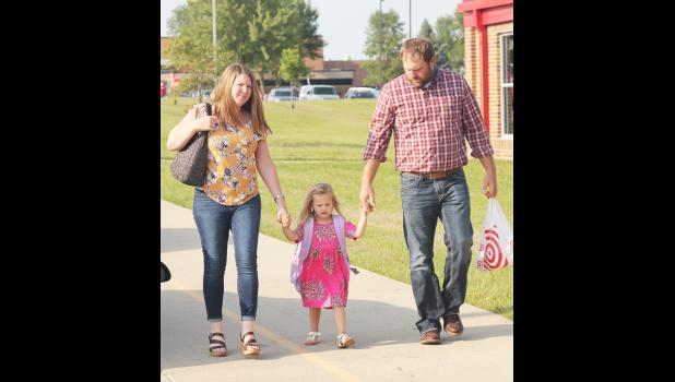 Kara and Jon Meiners arrive with their daughter, Abigail, for the back to school open house Wednesday evening at the Harlan Community Primary building. Abigail is a preschool student this year.
