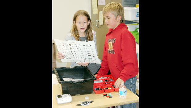 Allyson Ludwick and Kayden Erwin look over the parts in their EV3 robot kits.  They will learn the precise steps in building their robots this fall, and learn to program and code instructions to operate the EV3.