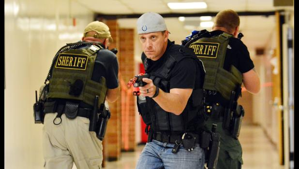 Harlan Police Officer Bill McDaniel keeps alert as his team searches for victims.