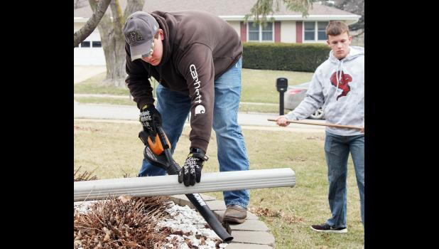 Jack Buman (left) and Tyler Buman clean up a rock area around a home.