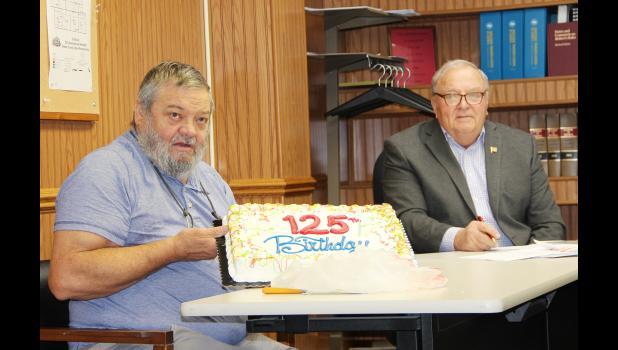 Chamberlain presents the cake to the supervisors.  Shown is supervisor Roger Schmitz.