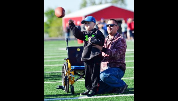 Jaxon Rold, who is battling cancer, throws the football during the elementary track meet with his father, Trent.