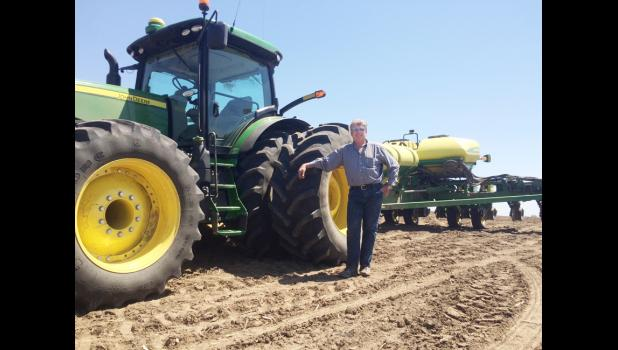 Randy Pryor stands in front of his corn planter in Woodbine.  Pryor said it has been a cool and wet planting season.  (Photo by Jacey Goetzman)