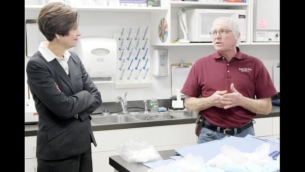 Smitty Bee's Owner Doug Schmitz (right) speaks with Iowa Governor Kim Reynolds during her tour of Smitty Bee Honey Inc. in Defiance.