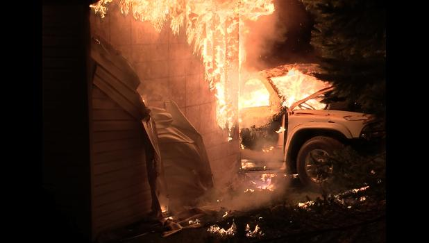 The vehicle fully engulfed in flames.