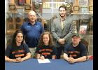 HCHS senior and Midland University swimming signee Abby Bruck is seated next to her parents, Matt and Michelle Bruck, Harlan. Standing behind Abby are Lewis Central coach Bruce Schomberg (left) and Midland coach Ryan Bubb.