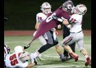 HCHS defensive lineman Allen Fries (55) refuses to let go of Osky quarterback Cole Henry's jersey as Alex Schechinger (42) helps make the tackle during last week's playoff game.