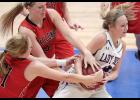 AHSTW freshman Claire Harris (right) rips the ball away from HCHS seniors Lexie Holloway (center) and Lexi Larsen during Tuesday's Hall of Pride Scrimmage.