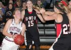 Exira-EHK senior Kealey Nelson (left) drives to the basket as Ar-We-Va's Jadeyn Smith defends and Emilee Danner looks on. Nelson led the Spartans with 18 points, 10 rebounds and five assists as the team won 78-44 and improved to 3-0. (Photo by Kim Wegener)