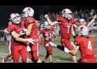 Harlan Community players Connor Frame (2), Teagon Kasperbauer (11), Jameson Bieker (34), Brad Curren (7) and Ashton Lyon (4) start the post-game celebration Friday night after Lewis Central's last-second pass into the end zone was ruled incomplete, giving the Cyclones a thrilling 36-29 come-from-behind victory at Merrill Field.