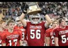 Flanked by teammates Kevin Campbell (17) and Joey Arkfeld (54), Harlan Community senior Caleb Brouse carries the Cyclones' state semifinalist trophy off the field following Thursday night's 41-39 loss to Pella in a Class 3A semifinal playoff game at the UNI-Dome. HCHS finished the season 10-2 overall. (Photos by Mike Oeffner)