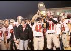 Harlan Community seniors Alex Schechinger (42) and Cody Christensen (81) hold up the Cyclones' Class 3A playoff qualifier trophy following Friday's 9-7 first-round loss at Dallas Center-Grimes. HCHS finished the season with an overall record of 7-3. (Photos by Mike Oeffner)