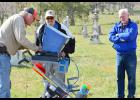 Rick Norland, president, Construction Solutions, Inc., Kansas City, utilizes ground penetrating radar to find graves in the Holcomb Cemetery while WIPCA members Ron Chamberlain and Craig Poole (right) watch the progress.
