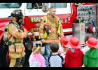 Firefighters Kristi Pedersen and Mike Butler show students at Harlan Community Elementary School Primary some of the equipment used by fire personnel.