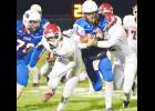 AHSTW quarterback Blake Osbahr (12) fights for rushing yardage during last week's playoff win over Newman Catholic as Caden Larson (70) looks to make a block.